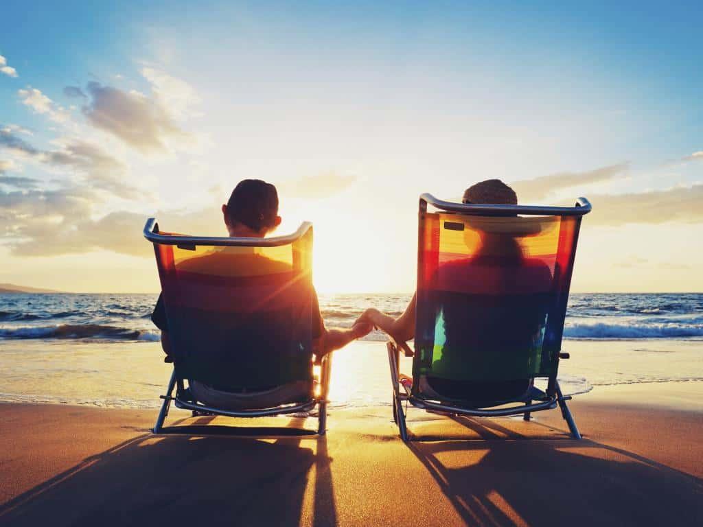 feliz pareja sentada en la playa al atardecer y tomados de la mano