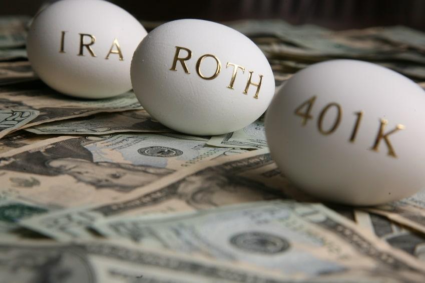 huevos chapados en oro con inscripciones en una pila de dinero en efectivo, marcados Roth, IRA y 401k