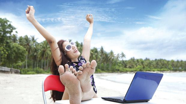 happy woman working on a laptop at the beach