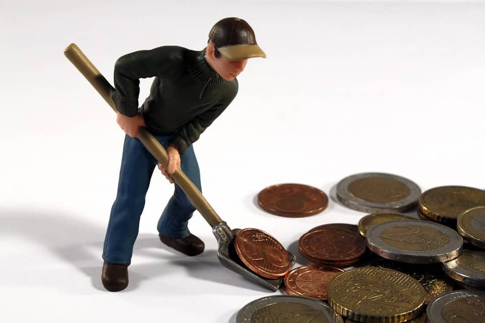 miniature of man digging coins