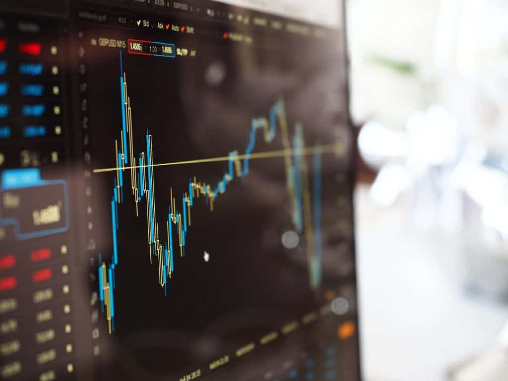 blue and yeallow graph on stock market monitor