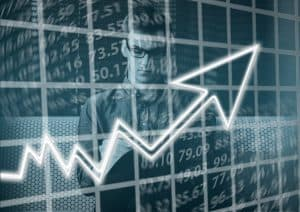 A man who needs books for new investors stands in front of a screen with numbers and an arrow point up.